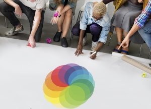 A woman writes on a pad while reviewing the color wheel for her website design