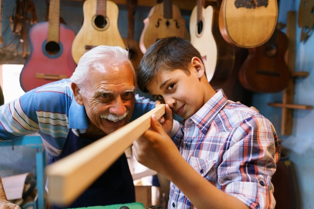 Grandpa showing grandson family business guitars